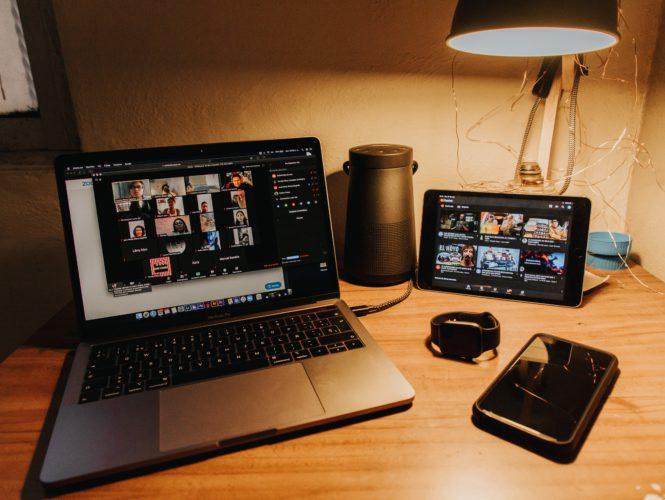 Zu sehen ist eine Schreibtisch mit verschiedenen Utensilien, darunter ein Laptop, auf dem eine Zoom-Videokonferenz läuft. Bild: Unsplash/Gabriel Benois
