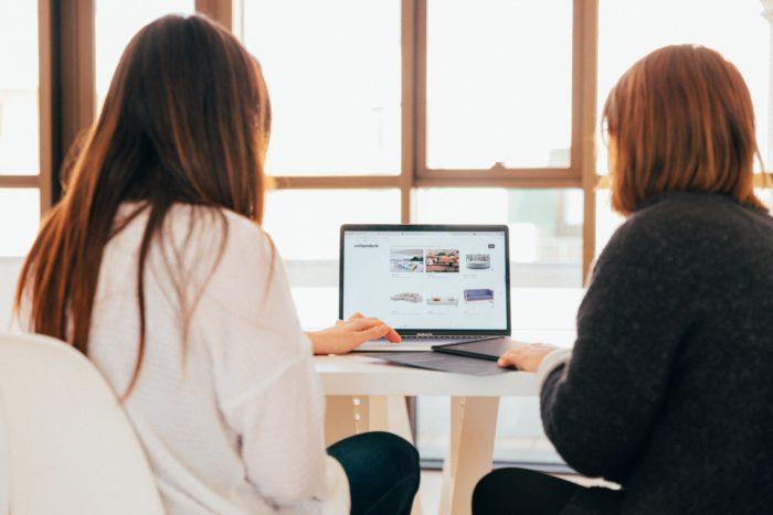 Microsoft Teams-App: Zwei Frauen sitzen gemeinsam an einem Laptop. Bild: Unsplash / KOBU Agency