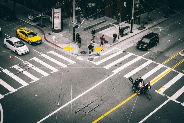 Symbolbild für tracking-Apps: Straßenkreuzung von oben, Menschen. Bild: Unsplash/Yoel J Gonzalez