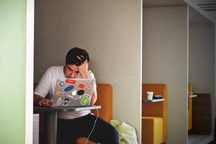 Ein junger Mann sitzt gestresst vor seinem Computer. Er sollte To-Do-Listen-Apps nutzen. Bild: Unsplash/Tim Gouw