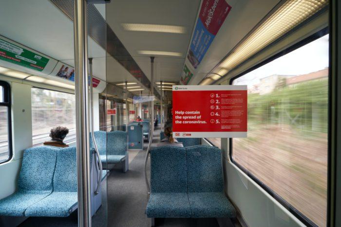 Zu sehen ist ein recht leeres Zugabteil, ein Poster zeigt den richtigen Umgang im Zug in Zeiten des Coronavirus. Die DB-Navigator-App schützt vor vollen Zügen. Bild: Unsplash/Dmitry Dreyer