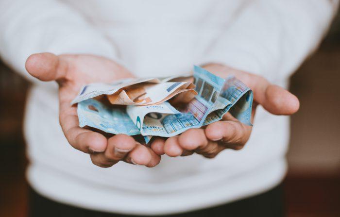Das Bild zeigt eine Hand mit Bargeld. Bild: Unsplash/Christian Dubovan
