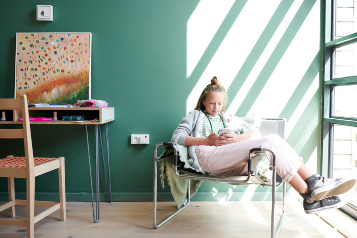 Fritz!Box-Update: Mädchen im Zimmer mit Mobilgerät. Bild: AVM