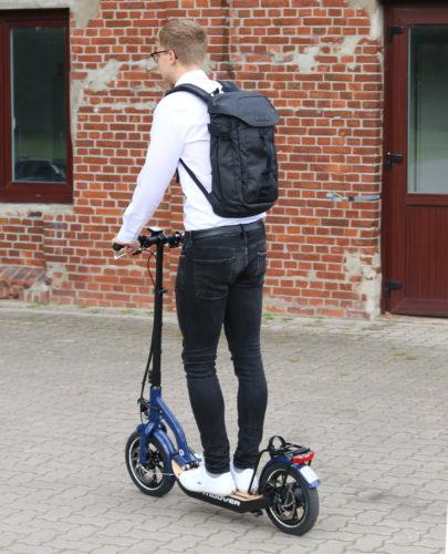 zu sehen ist ein Mann auf einem eScooter, auf dem Rücken trägt er einen Sol-Lite-Rucksack. Bild: Targus