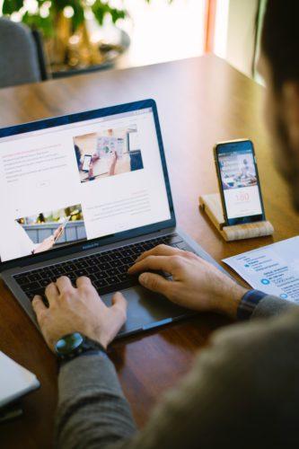 Sicherheits-Apps: Hande auf Laptop-Tastatur, Smarthone steht daneben in Ladestation. Bild: Unsplash/Agefis