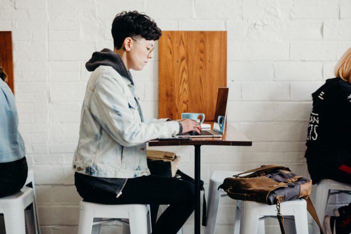 Eine Frau arbeitet im Café und beweist: Remote Work im Kleinbetrieb funktioniert. Bild: Unsplash/Brooke Cagle