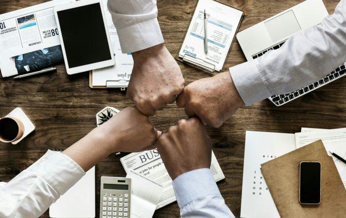 Draufsicht auf Schreibtisch im Büro mit vier Fäusten, die sich treffen. Bild: Pixabay