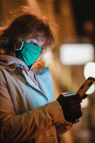 Frau mit Handy und Mundschutz schaut nach der COVID-19-Verbreitung. Bild: Unsplash/Adam Nieścioruk
