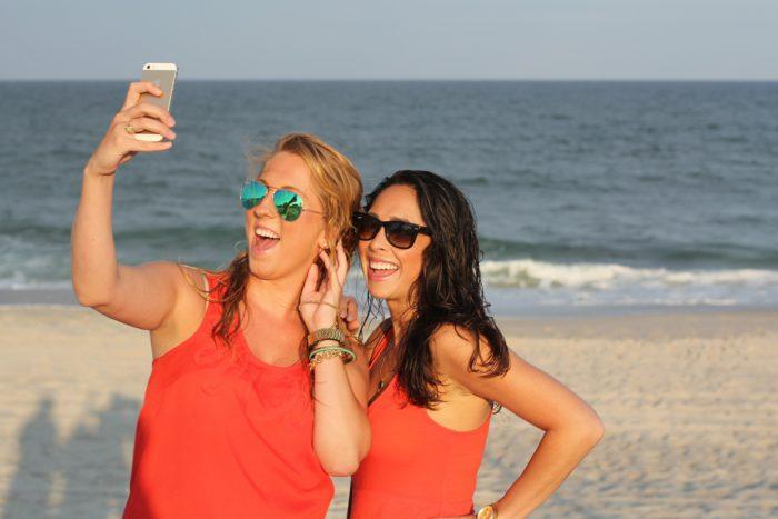 TikTok-Einstellungen: Zwei junge Frauen am Strand filmen sich. Bild: Pixabay
