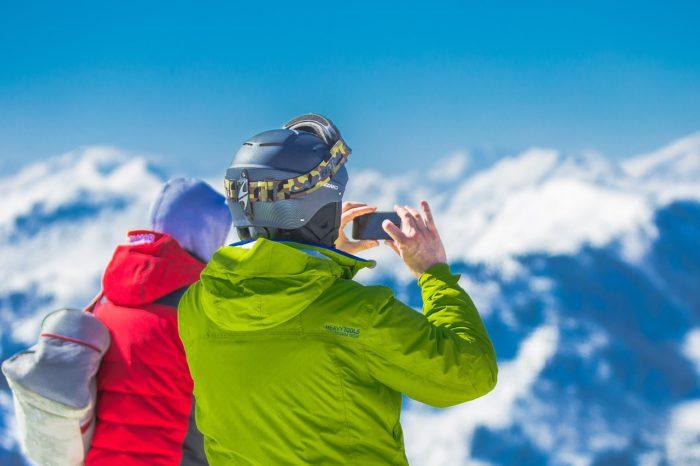 Touchscreen-Handschuhe: Zwei Personen mit Ski-Kleidung und Helm im Schnee, Einer hält das Handy und macht ein Foto. Bild: Pixabay