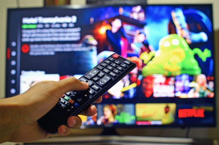 Lineares Fernsehen: Bunter Netflix-Bildschirm und Hand mit Fernbedienung. Bild: Pixabay