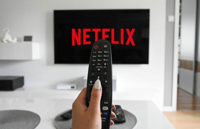 Lineares Fernsehen: Hand hält Fernbedienung, die auf einen Bildschirm mit Netflix-Logo ausgerichtet ist. Bild: Pixabay