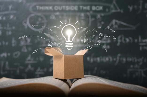 Intel® Education: Aufgeschlagenes Buch, vor grüner Schultafel, geöffneter Karton mit erleuchteter Glühbirne. Bild: © Intel®