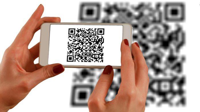 Barcode-Scanner-App: Frauenhände halten Handy, Display zeigt QR-Code, der gescannt wird. Bild: Pixabay