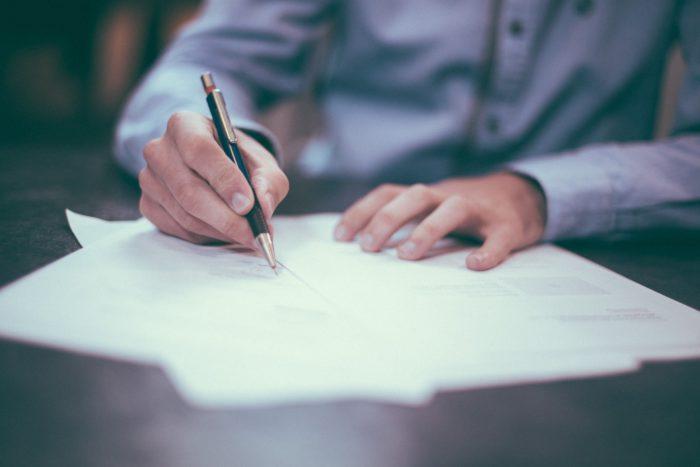 Digitale Signatur: Mann unterschreibt mit Kugelschreiber auf einem Blatt Papier. Bild: Unsplash/Scott Graham