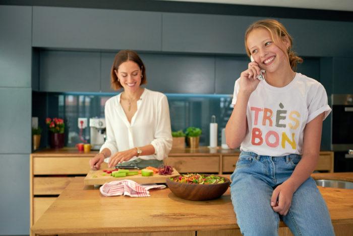 Mutter und Tochter in der Küche, Tochter mit Telefon. Bild: ©AVM