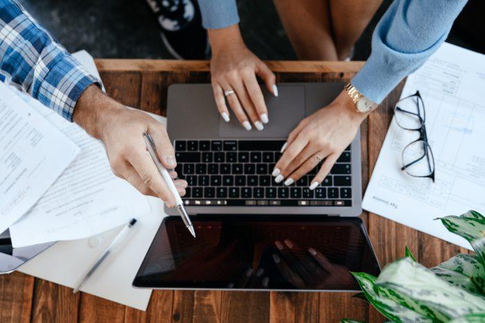 Bring Your Own Device: Zwei Personen arbeiten an einem Laptop. Das Bild wurde von oben fotografiert und nur die Hände sind sichtbar. Bild: Pexels/ Alexander Suhorucov