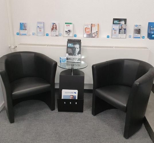 Zwei Sessel mit Tisch, dahinter ein Regal mit Info-Material. Bild: Frank Neumann