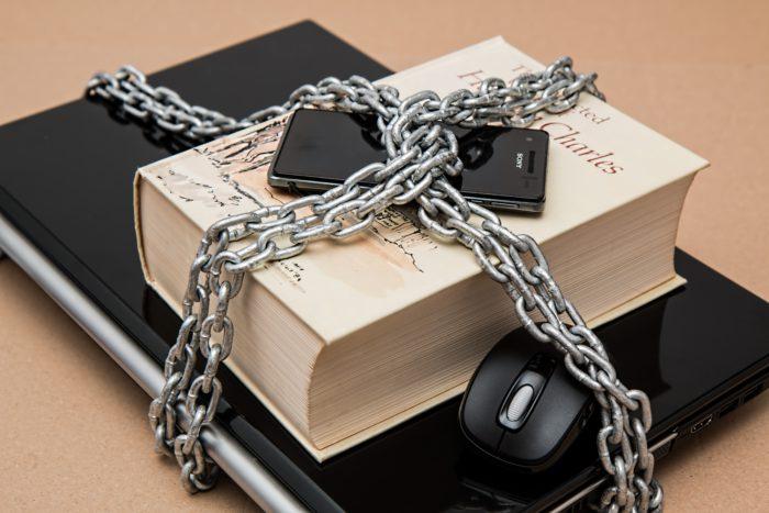 Bring Your Own Device. Laptop, Buch und Handy in Ketten gelegt. Bild: Pexels