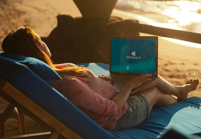 Workation: Frau liegt am Strand auf einer Liege und hat ihren Laptop auf dem Schoß. Bild: Pexels