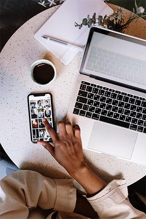 iPhone-Tricks. Geöffnete Galerie auf dem iPhone, Macbook und Kaffee aus der Vogelperspektive. Hand scrollt in der Galerie. iPhone-Tricks.