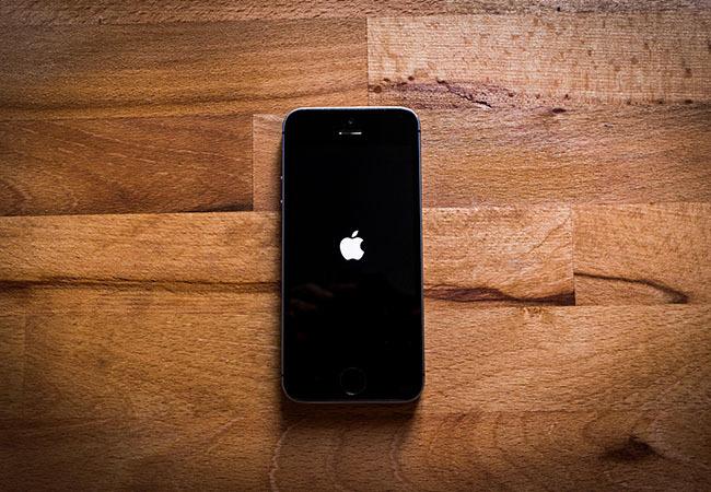 iPhone-Tricks: Schwarzes iPhone mit dem Apple-Logo auf einer Holzoberfläche. Bild: Pexels