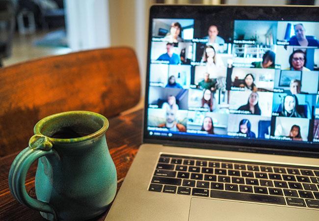 Google Chat: Laptop, Bildschirm mit Meeting, Krug neben dem Laptop. Bild: Unsplash/Chris Montgomery