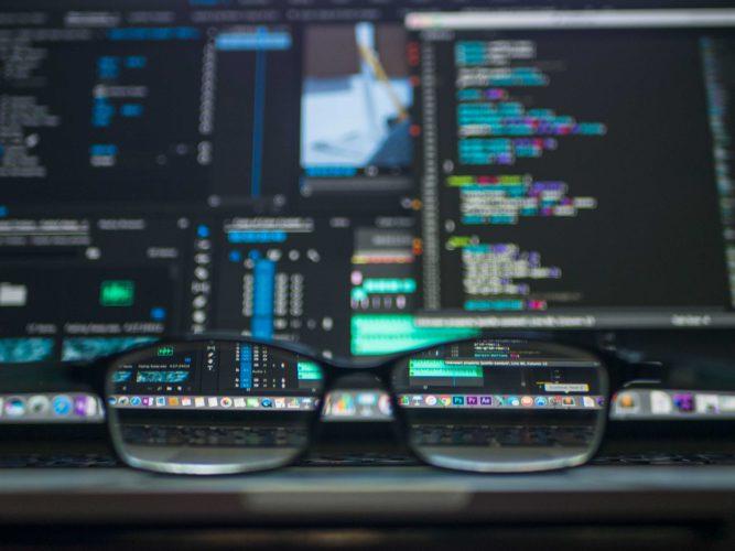 RaaS: Mehrere Monitore mit binären Zeichensätzen und davor eine Brille. Bild: Unsplash/Kevin Ku