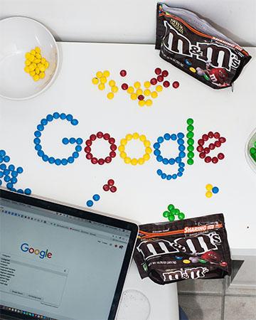 Laptop mit geöffneter Google-Suche und Google-Schriftzug aus m&m's gelegt. Bild: Unsplash/lalo Hernandez