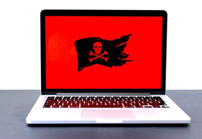 RaaS: Laptop mit rotem Bildschirm und schwarzer Piratenflagge. Bild: Unsplash/Michael Geiger