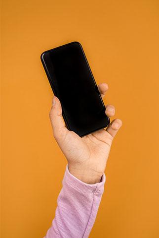 Kurz-URL: Oranger Hintergrund, Hand mit schwarzem Handy. Bild: Pexels/Sound On