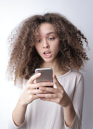 Weiblicher Teenager blickt erschrocken auf das Handy in der Hand. Bild: Pexels/Andrea Piacquadio