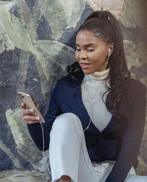 Voicemail: Junge Frau mit Kopfhörern blickt auf ihr Handy. Bild: Pexels/George Milton