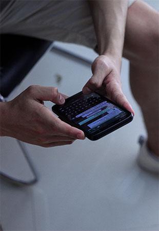 Hände halten Smartphone, WhatsApp ist geöffnet. Bild: Unsplash/Asterfolio