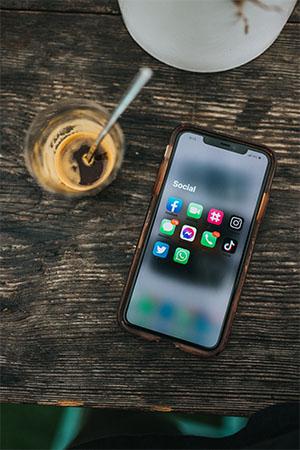 Handy auf dem Tisch, Display mit App-Symbolen, Kaffeeglas. Bild: Unsplash/Nathan Dumlao