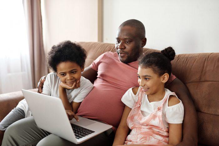 Netflix-Tricks. Ein Vater sitzt mit seinen zwei Töchtern im Arm vor dem Laptop. Bild: Pexels