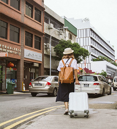 Frau mit Hut, Rucksack und Koffer geht durch die Straße einer Stadt. Bild: Pexels/Tranmautritam