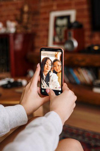 WhatsApp-Speicher. Zwei Personen machen ein Selfie, welches aber nur auf dem Handy sichtbar ist. Bild: Pexels