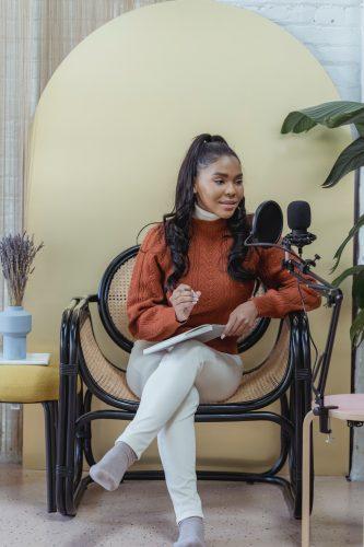 Polywork. Frau sitzt vor einem Mikrofon und hat Schreibunterlagen in ihrem Schoß liegen. Bild: Pexels