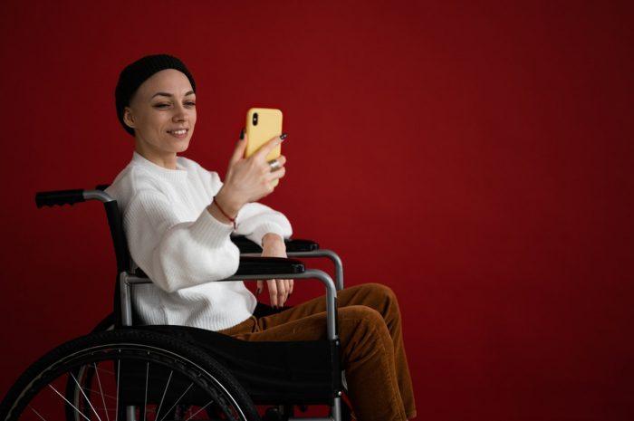 Kameraschalter. Lächelnde Frau sitzt im Rollstuhl vor ihrem Handy und kann nur einen Arm benutzen. Bild: Pexels