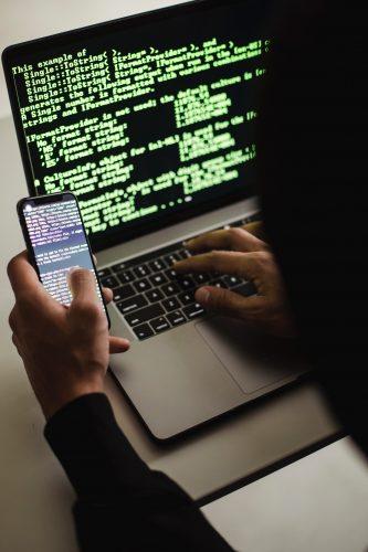 Vultur. Ein Cyberkriminelle sitzt vor einem Handy und Laptop. Ein Code ist auf beiden Geräten sichtbar. Bild: Pexels