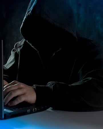 Brute Force: Anonymer Computer-Hacker im Kapuzenpulli. Er benutzt einen Laptop für einen Cyberangriff und ruft mit dem Handy an. Bild: Unsplash/Bermix Studio