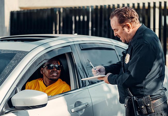 Führerschein-App: Polizist steht am Auto und kontrolliert den Fahrer. Bild: Pexels/Kindel Media