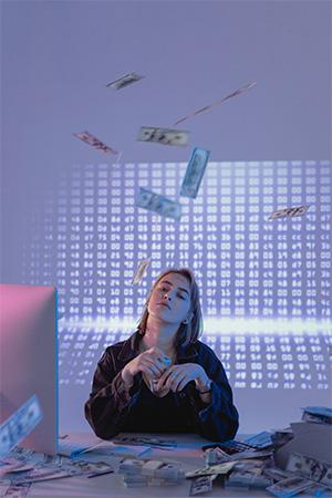 Trojaner GriftHorse: Frau am Schreibtisch mit PC und vielen Geldsscheinen. Bild: Pexels/Tima Miroshnichenko