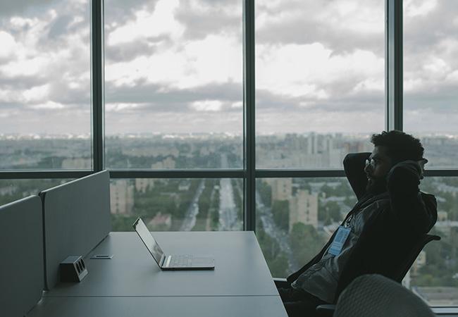 Mann am Schreibtisch mit Laptop vor Fensterfront mit Blick über eine Stadt. Bild: Pexels/Cottonbro