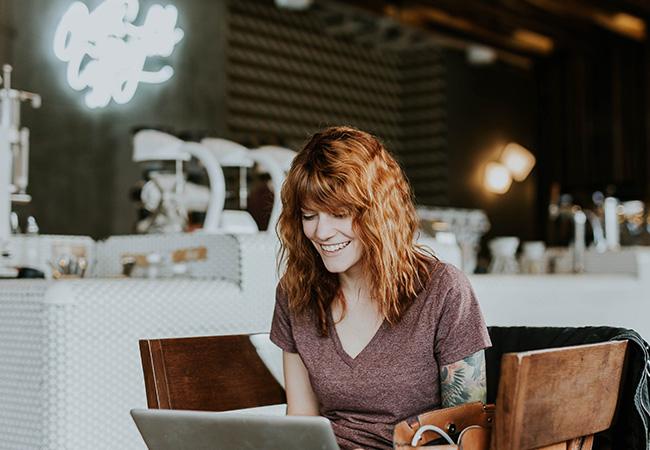 Hybrides Arbeiten: Frau sitzt im Café arbeitet am Laptop. Bild: Unsplash/Brooke Cagl