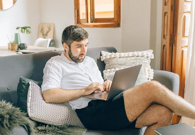 Hybrides Arbeiten: Mann in kurzen Hosen mit einem Laptop auf dem Sofa. Bild: Pexels/Nataliya Vaitkevich